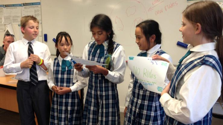 Five Australian school children presenting their work. They are of many cultural backgrounds.