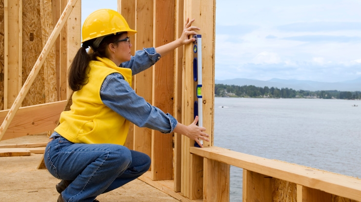 Female builder or architect measuring a window on a house being built.