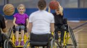 Kids on a wheel chair playing basketball